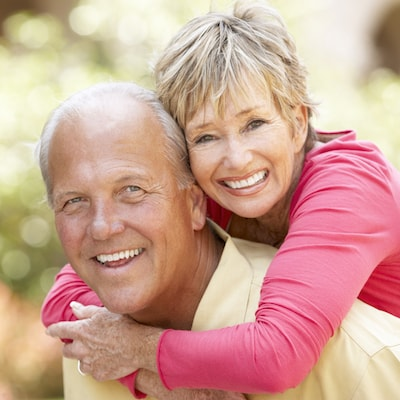 Old couple laughing with their new dentures after their family dentistry appointment