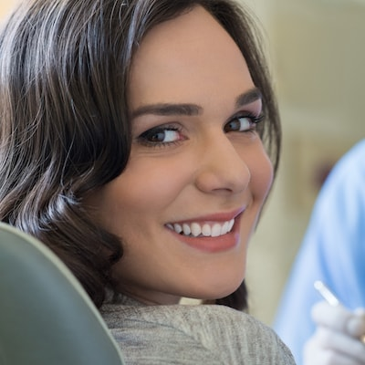 Young woman smiling as she has an exam as part of family dentistry in East Orlando