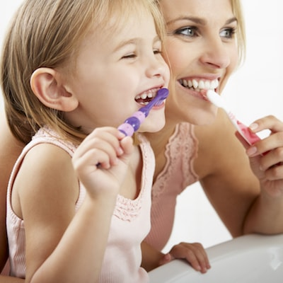 Mother and daughter brushing their teeth as they prepare for their hygiene and family dentistry visit