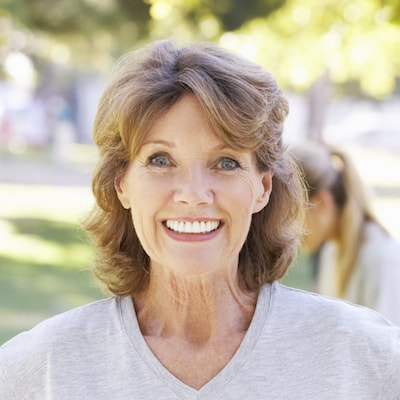 Older woman showing off her new smile after family dentistry and an implant restoration