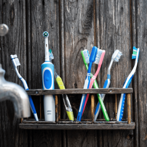 Toothbrushes on a ledge against a wall