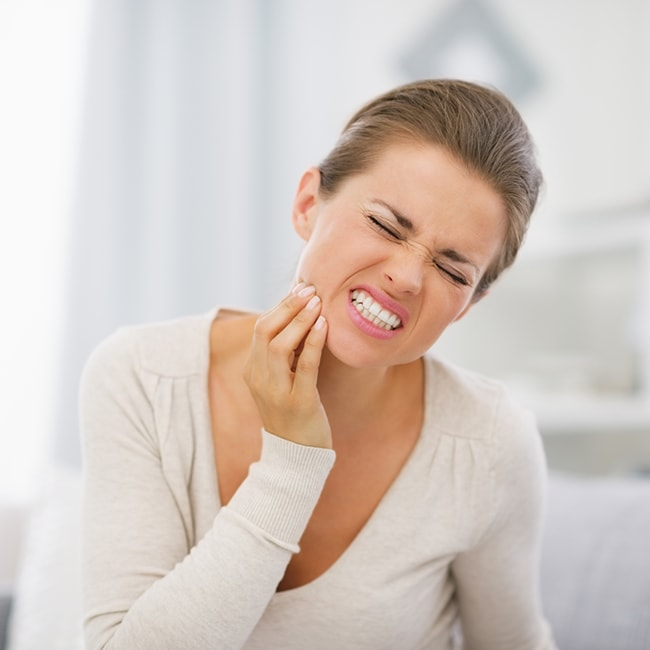 Women holder her face in pain from a dental emergency