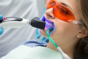 Woman undergoing professional teeth whitening in a dental office