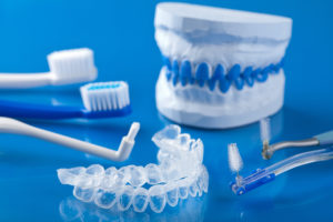 Various types of dental tools, and aligners on a blue background