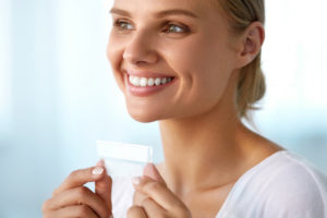 woman smiling while holding up a teeth whitening strip