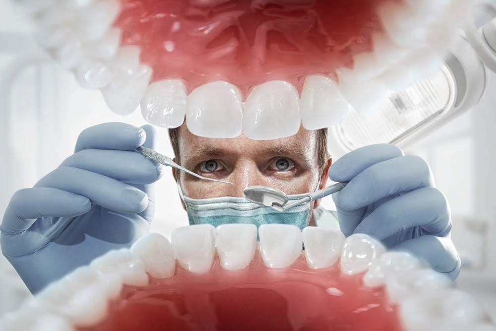 A dentist looking inside a patients mouth during an exam