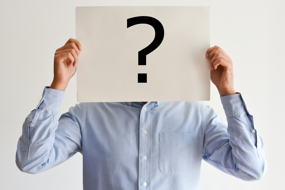Man holding a sign with a question mark in front of his face