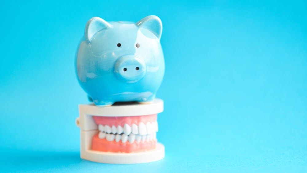 A blue piggy bank on top of a plastic mouth