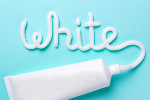 A tube of toothpaste on a light blue background with the word white written on it.